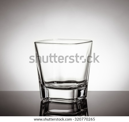 empty glass of whiskey on black table with reflection on white background, time of relax with whisky - stock photo