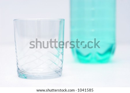 empty glass with green plastic bottle of water