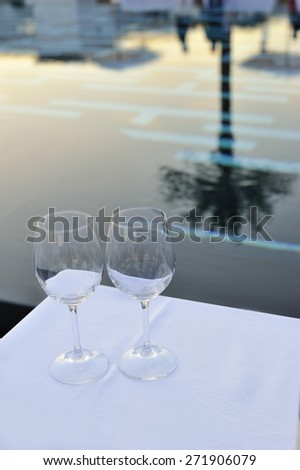 Empty glasses and pool on sunset  - stock photo