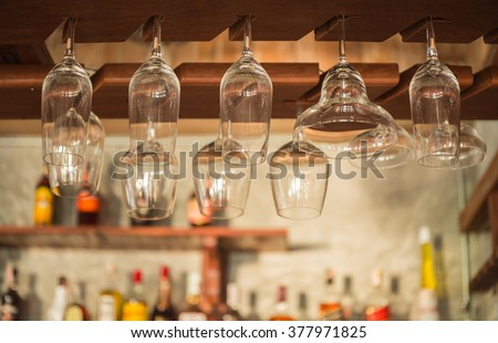 Empty glasses for wine and soft drink above a wooden bar rack  - stock photo