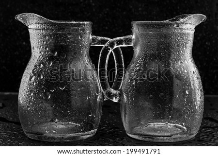 Empty glasses in water drops on black background - stock photo