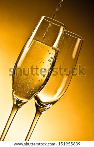 empty glasses of champagne and one being filled against golden background - stock photo