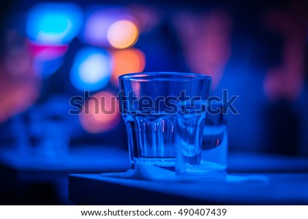 Empty glasses on a table in the club, abstract blurry blue lights in the background