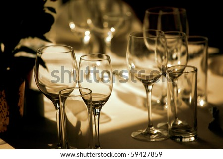 Empty glasses on restaurant table lit with orange light - stock photo