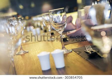 Empty glasses set in restaurant, Defocused foreground , Ambient lighting - stock photo
