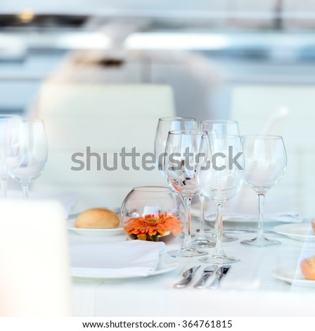 Empty glasses set in restaurant in high key - stock photo