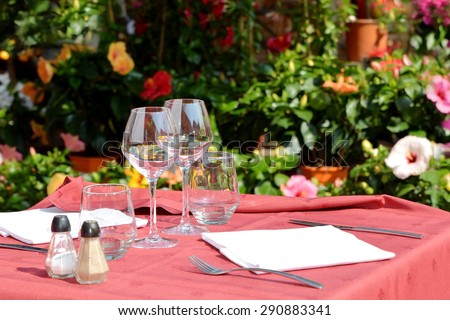 Empty glasses set in street terrace of restaurant, Provence, France. - stock photo