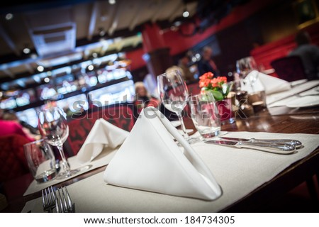 Empty glasses set with napkin in fine dining restaurant decorated in red style - stock photo