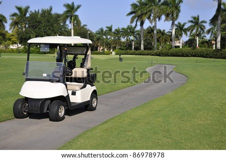 Empty golf cart sitting on a macadam path by a golf course - stock photo