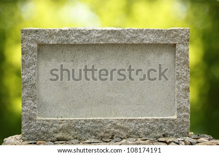 Empty granite signboard with border & frame. The granite is placed in natural outdoor settings showing vibrant green blurred background plants and sunlight effect. - stock photo
