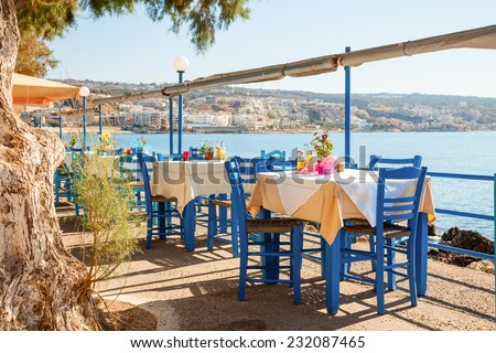 Empty greek cafe terrace in Heraklion, Crete overlooking the sea with typical wooden chairs