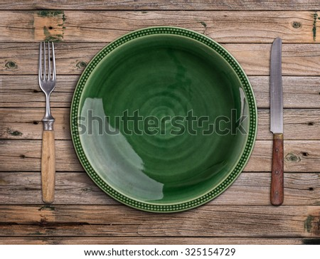 Empty green plate on a wooden table - stock photo