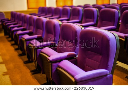 Empty hall for presentation with purple armchairs - stock photo