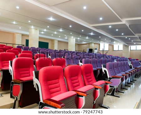 Empty hall for presentation with red and purple armchairs - stock photo