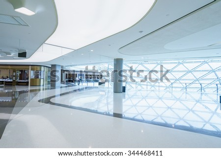 empty hallway with a huge billboard and abstract ceiling in modern shopping mall - stock photo