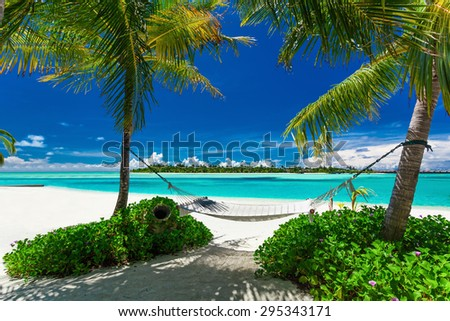 Empty hammock between palm trees on tropical beach with amazing lagoon - stock photo