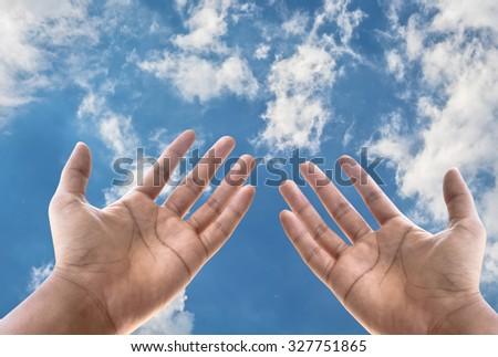Empty hand on blue sky background - stock photo