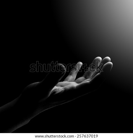 empty hand waiting for helping ,with light from right side on black background  - stock photo
