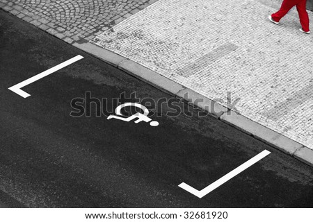 empty handicapped parking lot on a street - legs of bypasser on pavement - stock photo