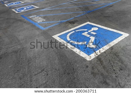 Empty handicapped parking spaces,disabled icon.Black asphalt parking lot.Rough texture surface,tire marks,oil stains.Blue striped lines,no parking area.Words and pictorial information.  - stock photo