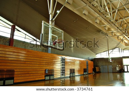 Empty high school gym with basketball hoop and bleachers - stock photo