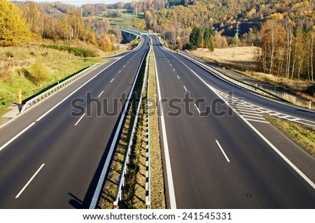 Empty highway between deciduous trees in autumn colors, in the distance electronic toll gates, view from above - stock photo