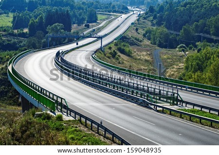 Empty highway between forests in the landscape, in the middle of the highway electronic toll gate, in the distance on the highway motorcycle, car and Bridges - stock photo