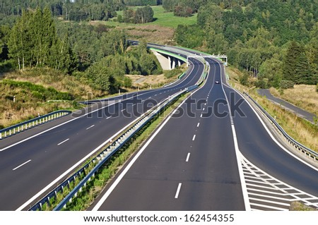Empty highway between forests in the landscape, in the middle of the highway electronic toll gate and bridge, in the distance on the highway car, view from above - stock photo