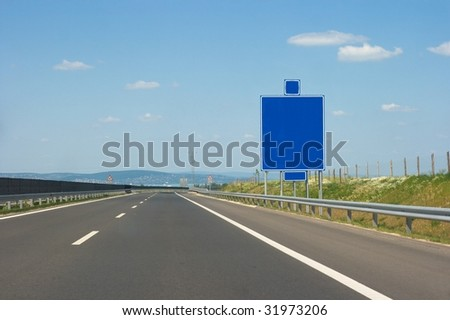 Empty highway lanes and blank signboard - stock photo