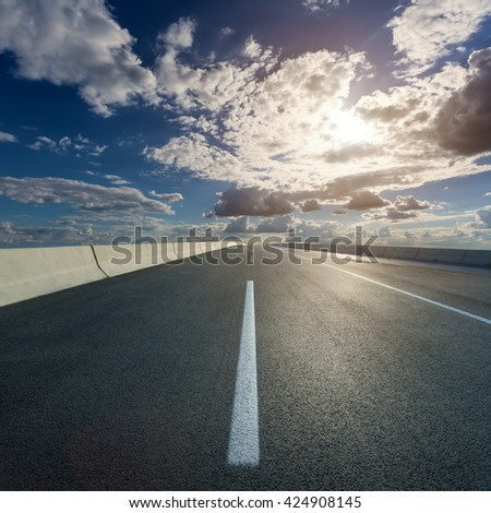 Empty highway leading to the beautiful clouds, against the setting sun at idyllic sunny day. - stock photo