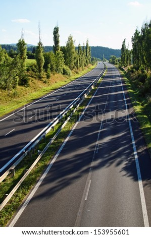 Empty highway lined with a row of trees, tree shadows thrown on the highway, view from above, car in the distance, forested mountain in the background - stock photo