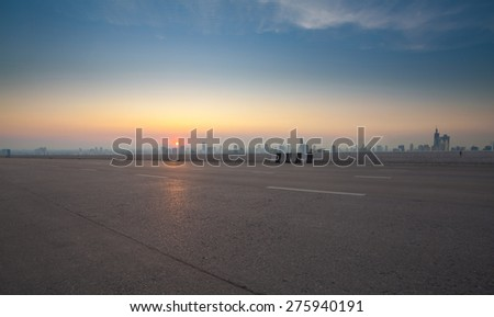 Empty highway road with city sunset background - stock photo