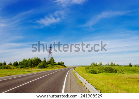 Empty highway stretching into the distance under a blue sky - stock photo