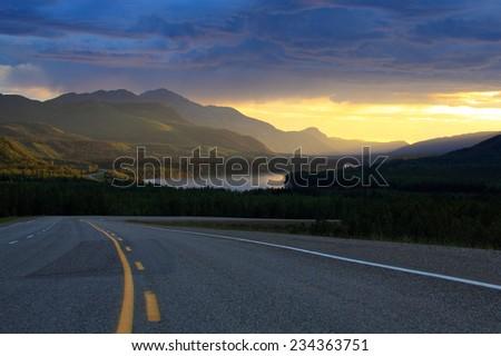 Empty highway through mountains - stock photo