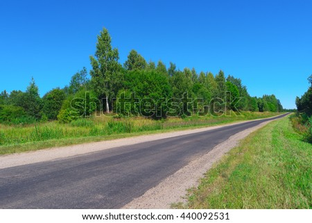 Empty highway through the trees, bushes and grass - stock photo