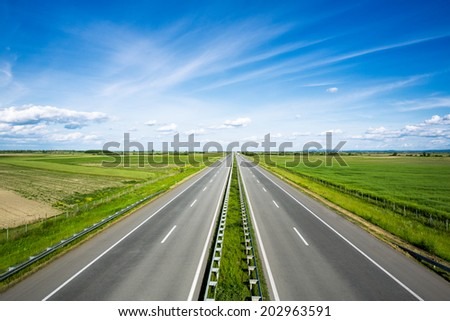 empty highway with green fields on both sides - stock photo