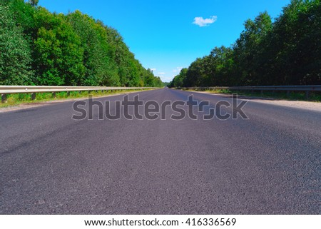 Empty highway with green forest on both sides - stock photo