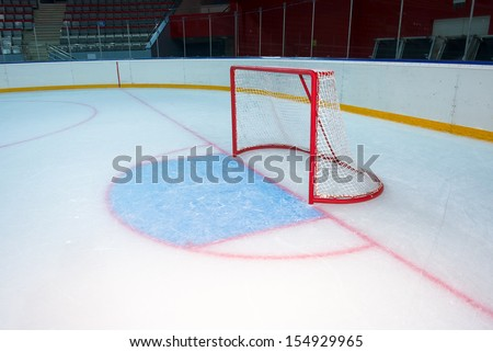 Empty hockey goal on ice rink. Side view - stock photo