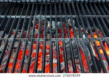 Empty Hot Barbecue Cast Iron Grill With Glowing Charcoal Background - stock photo