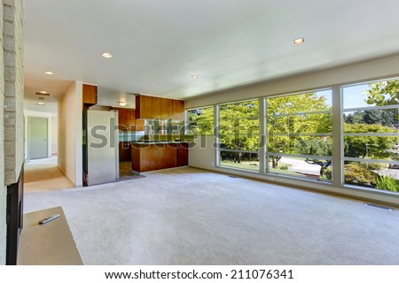 Empty house interior. Living room with glass wall and carpet floor. View of small kitchen area