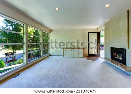 Empty house interior. Living room with glass wall. View of brick wall with fireplace