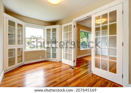 Empty house with new hardwood floor and white french doors. View of entrance hallway and small office room - stock photo