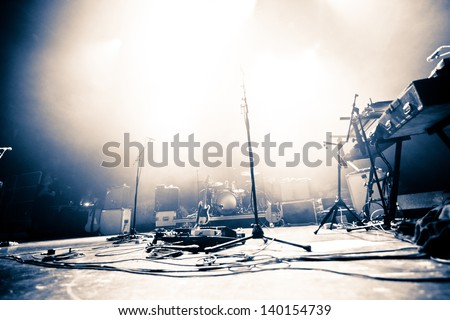 Empty illuminated stage with drumkit, guitar and microphones - stock photo