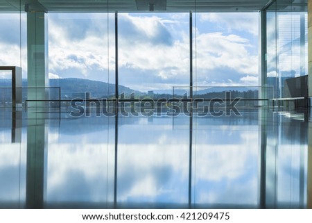 Empty interior of modern building with reflection of blue sky - stock photo
