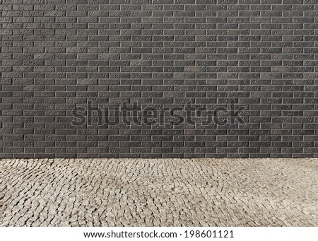 Empty interior with a wall from a dark brick with a pattern and a light floor paved by granite stones in a bright sunny day as background
