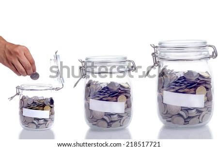 Empty jar coin and hand putting the coin into the jar - stock photo