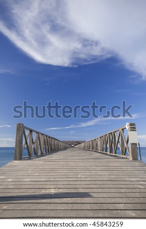 Empty jetty against blue skies in a tropical country - stock photo