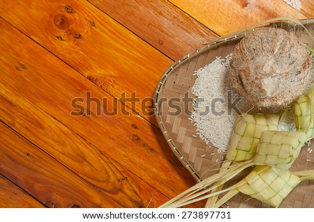 Empty ketupat or packed rice dumpling. Delicious traditional Malay ramadan or eid fitr food. Popular Malaysian food on bamboo mat and pine wood table. - stock photo