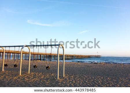 Empty kids swings at golden hour at Ventura sandy city beach near famous historic wooden pier, Ventura, California - stock photo