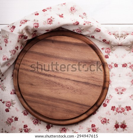Empty kitchen cutting board. Wooden table covered with tablecloth. View from top.  - stock photo